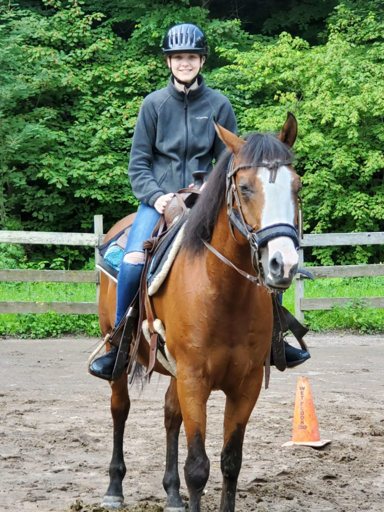 girl in riding gear posing on horse