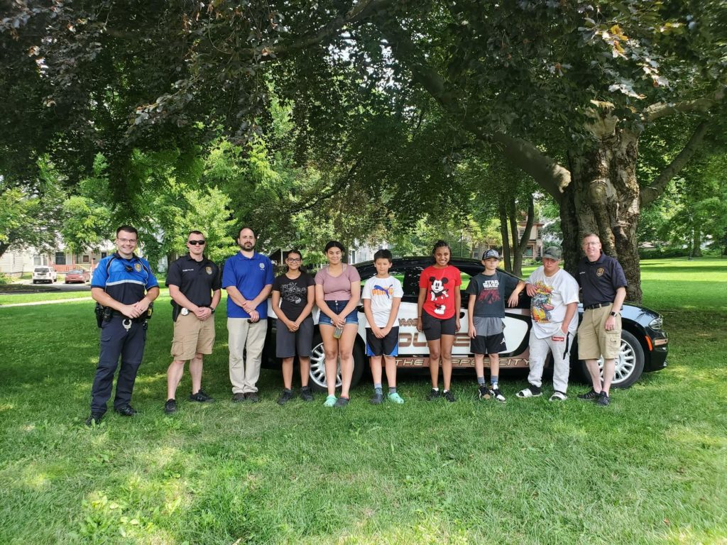 kids posing with rome police department officers in park