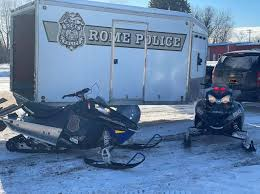 snow mobiles outside rome police department trailer