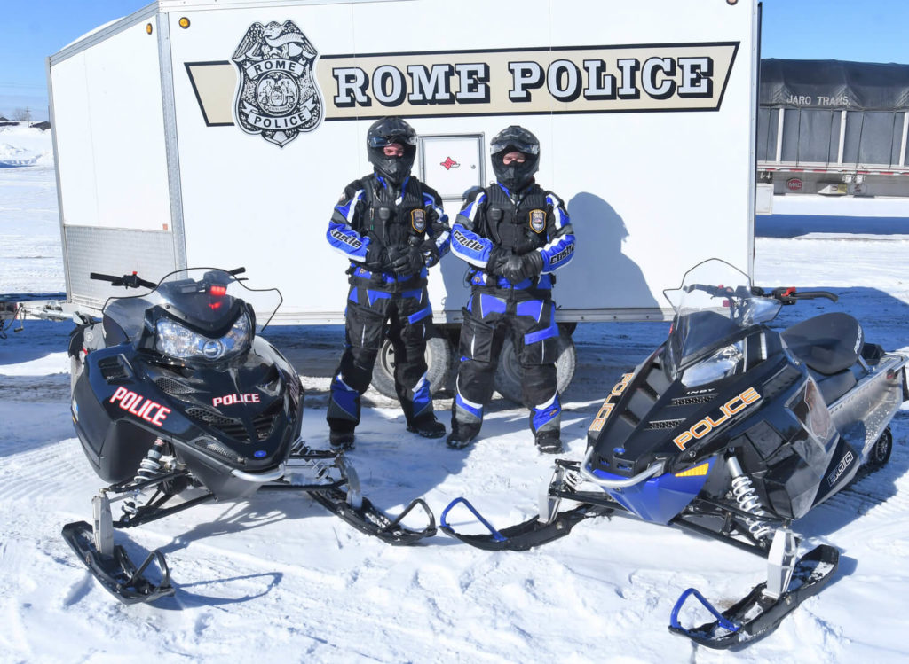 rome police department officers posing with snowmobiles in snow